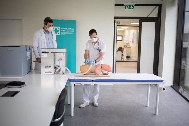 Dos operarios clínicos del proyecto de respiradores de SEAT muestran el funcionamiento de un respirador que han fabricado para los contagiados por coronavirus en un maniquí de simulación médica en las instalaciones de SEAT de Martorell