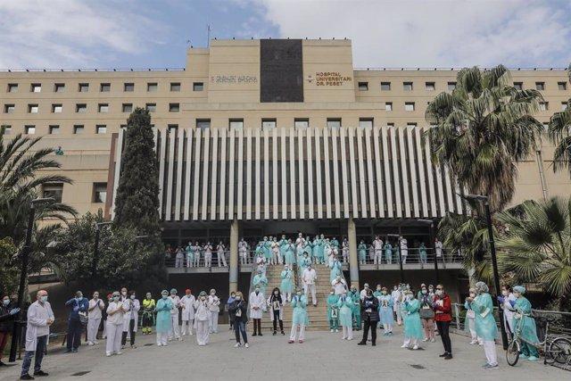 Sanitarios protegidos con mascarillas aplauden conmocionados tras el minuto de silencio en la entrada del Hospital Doctor Peset por la técnica de enfermería fallecida por coronavirus, en Valencia/Comunidad Valenciana (España) a 6 de abril de 2020.