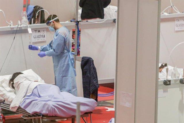Un sanitario protegido con mascarilla atiende a una paciente ingresada por coronavirus en el Hospital de Campaña montado en el recinto madrileño de IFEMA, en Madrid, (España).