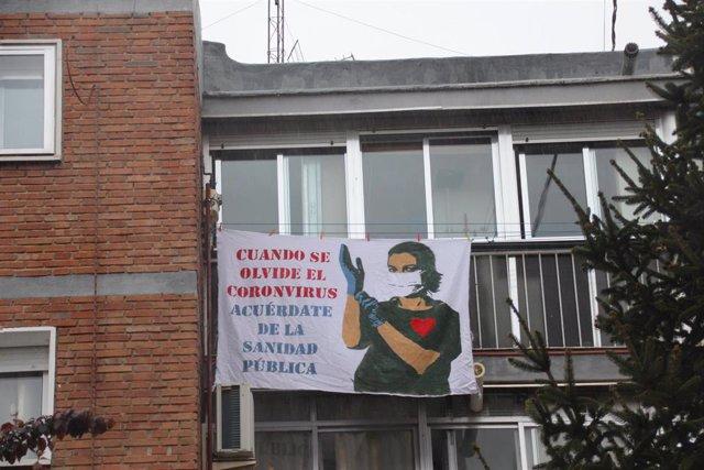 Sábana blanca con un dibujo de una sanitaria protegida con mascarilla y guantes y unas letras que dicen 'Cuando se olvide el coronavirus, acuérdate de la Sanidad Pública', en una ventana de Madrid por el Día Mundial de la Salud