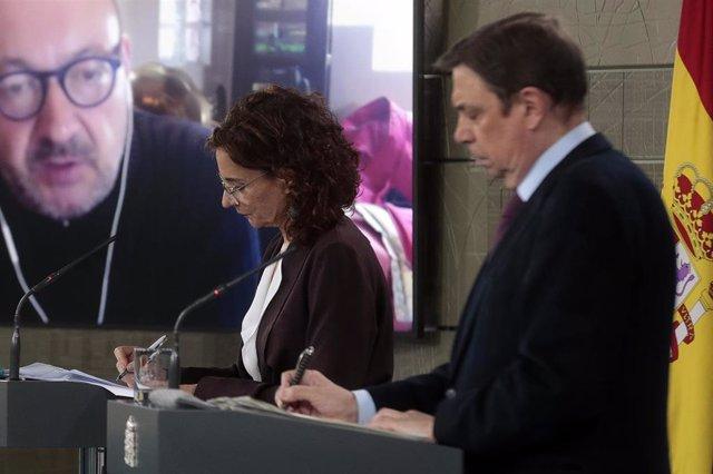 La ministra de Hacienda y portavoz del Gobierno, María Jesús Montero; y el ministro de Agricultura, Pesca y Alimentación, Luis Planas, en rueda de prensa tras el Consejo de Ministros, en el Palacio de la Moncloa, en Madrid (España) a 7 de abril de 2020.