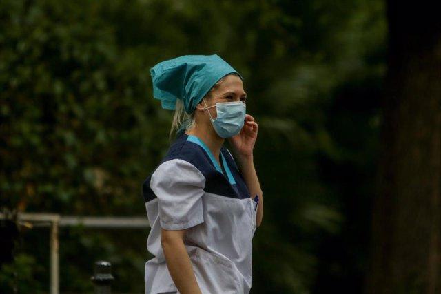 Una sanitaria protegida habla por teléfono en las inmediaciones de la Fundación Jiménez Díaz