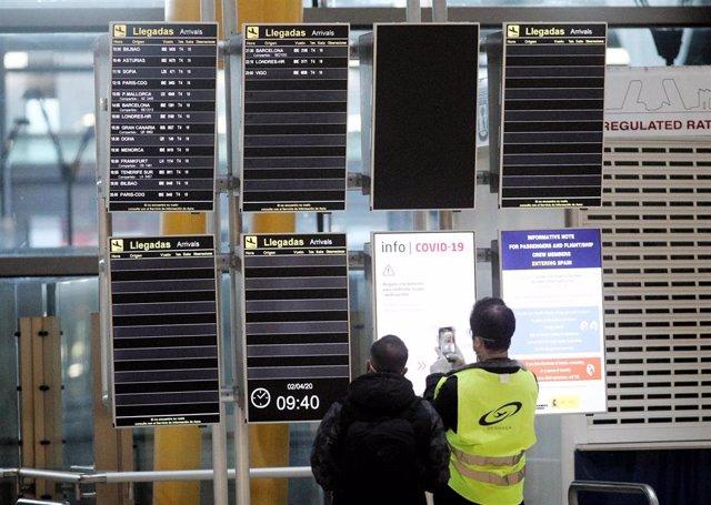 Uno de los dos trabajadores que observan los paneles informativos de los vuelos de la T4 de Adolfo Suárez Madrid-Barajas