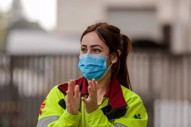 Una sanitaria protegida con mascarilla aplaude durante el homenaje en las inmediaciones de la Fundación Jiménez Díaz a todo el personal sanitario