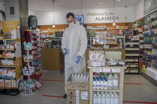 Un farmacéutico atiende una farmacia, abierta por ser esencial, durante la limitación total de movimientos salvo de los trabajadores de actividades esenciales, medida adoptada por el Gobierno como prevención del coronavirus. En Sevilla.