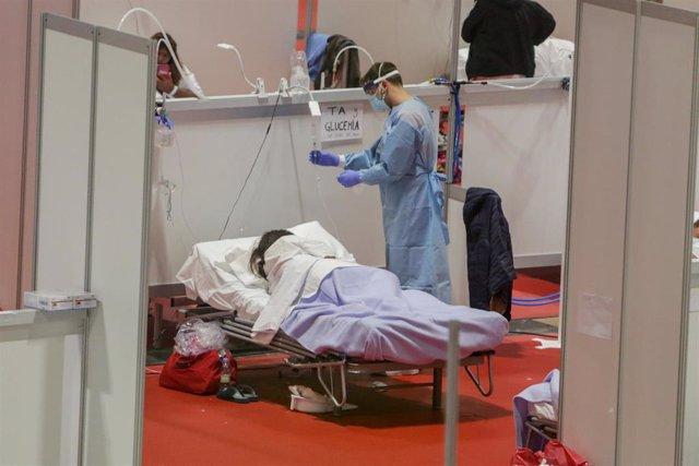 Un sanitario protegido con mascarilla atiende a una paciente ingresada por coronavirus en el Hospital de Campaña montado en el recinto madrileño de IFEMA, en Madrid, (España), a 3 abril de 2020.