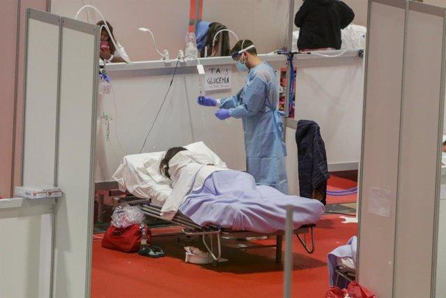 Un sanitari protegit amb màscara atén una pacient ingressada per coronavirus, a Madrid, (Espanya), 3 d'abril del 2020.