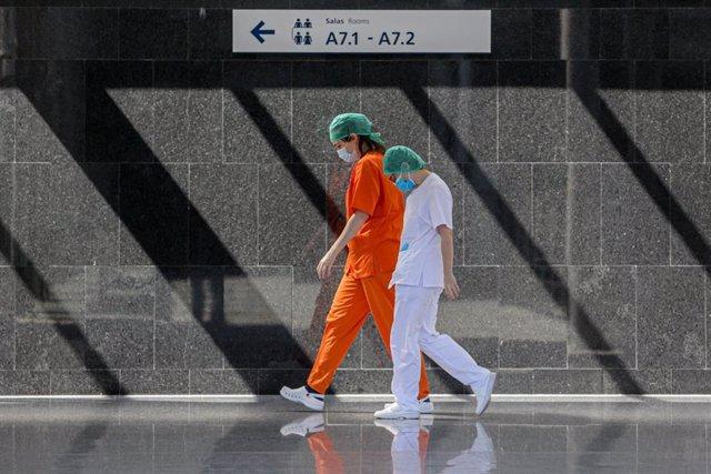 Dos sanitarios protegidos trabajan en el interior del Hospital temporal de la Comunidad de Madrid habilitado en IFEMA para pacientes con coronavirus, en Madrid (España) a 3 de abril de 2020.