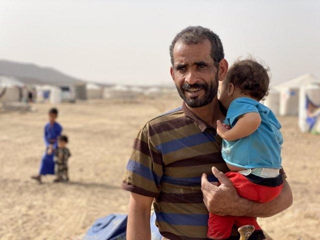 Un yemení desplazado por el conflicto junto a su hijo en el campamento de Marib.