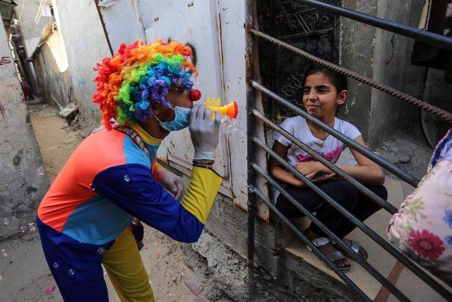 Un hombre palestino, disfrazado de payaso, entretiene a niños y niñas confinados en casa por el coronavirus.