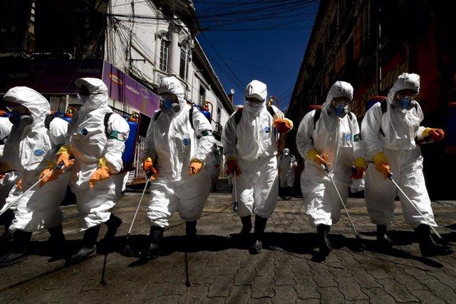 Trabajadores desinfectan las calles de La Paz, la capital de Bolivia, por el coronavirus.