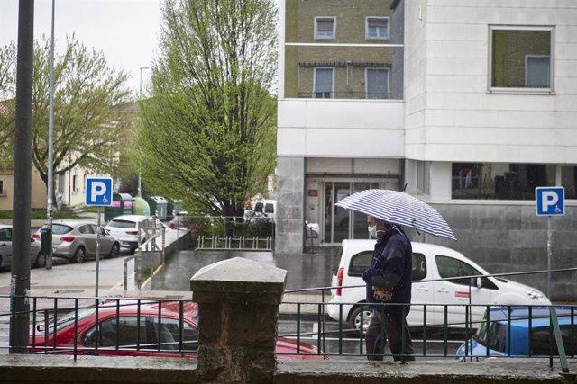 Un hombre con mascarilla camina protegiéndose con un paraguas por la lluvia  durante el Martes Santo y la cuarta semana del estado de alarma decretado por el Gobierno por la crisis del coronavirus, en Pamplona/Navarra (España) a 7 de abril de 2020.