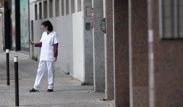 Una sanitaria con mascarilla consulta su móvil en la puerta del garaje del Hotel City House Florida Norte, un nuevo hotel medicalizado para la recuperación de pacientes afectados por coronavirus.