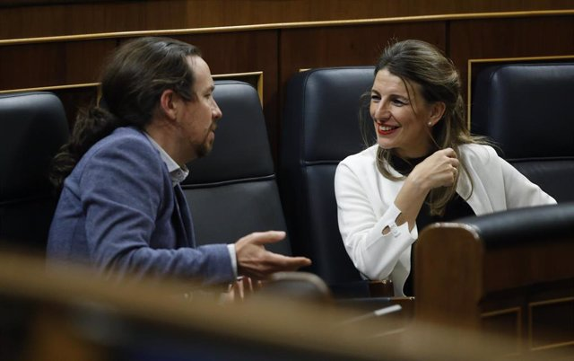 La ministra de Trabajo, Yolanda Díaz, habla con el vicepresidente de Derechos Sociales y para la Agenda 2030, Pablo Iglesias, durante el pleno celebrado este jueves en el Congreso de los Diputados.