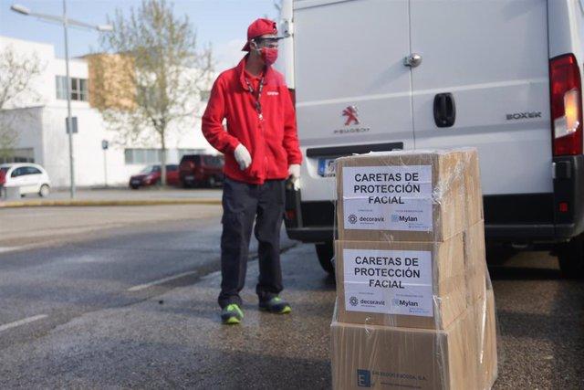 Un trabajador protegido con mascarilla deja unas cajas con caretas de protección facial.
