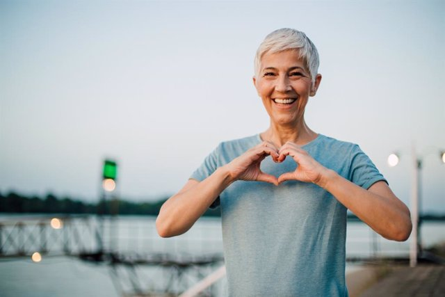 Active senior woman making a heart with her hands    Portrait of a happy senior woman making a heart shape with her hands after exercising on the riverbank.