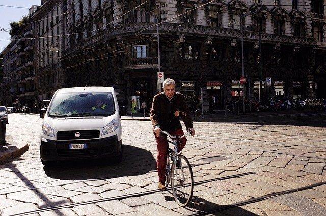 Coche y bicicleta circulando por una calle de Italia.