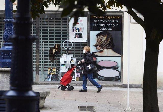 Una mujer camina por las calles de Santander totalmente vacías en el segundo día laborable del estado de alarma por el coronavirus, Santander, Cantabria (España), a 17 de marzo de 2020.