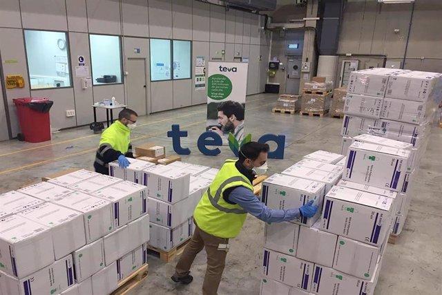 Dos trabajadores con mascarilla trabajan en el almacén de la compañía farmacéutica internacional TEVA