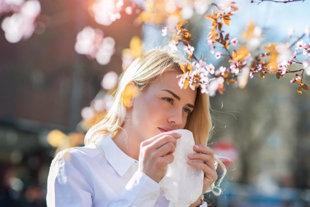 Woman sneezing in the blossoming garden    Woman sneezing into a tissue