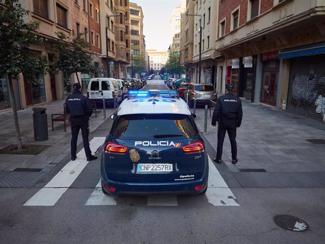 Dos agentes de la Policía Nacional junto a su coche