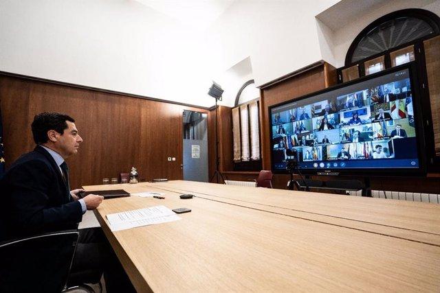 El presidente de la Junta de Andalucía, Juanma Moreno, participa en la quinta reunión telemática de la Conferencia de Presidentes autonómicos con el presidente del Gobierno, Pedro Sánchez, para abordar la crisis sanitaria del coronavirus