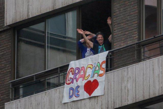 Dos vecinas sacan una pancarta en su casa como muestra de agradecimiento al personal sanitario que trabaja a destajo en la crisis del coronavirus en la Fundación Jiménez Díaz, durante la cuarta semana de confinamiento por la crisis sanitaria en el país,