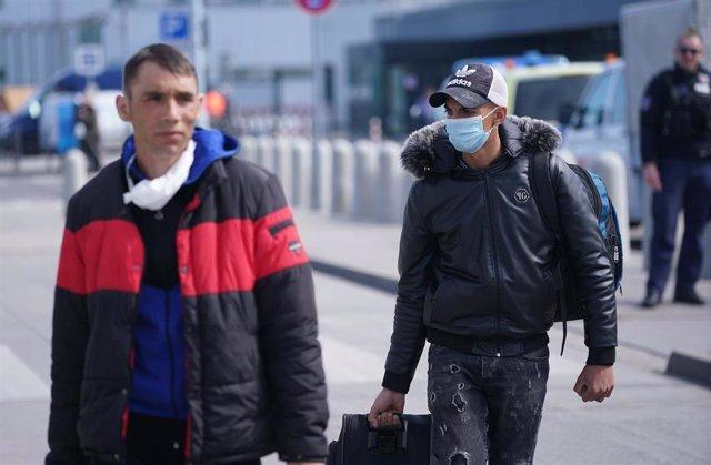 Temporeros rumanos con mascarilla