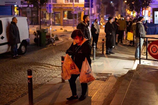 Una mujer con mascarilla tras comprar en un comercio en Estambul