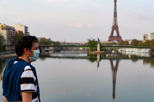 Un hombre con mascarilla cerca de la Torre Eiffel de París