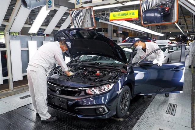 Dos hombres trabajan en una fábrica de la empresa japonesa Honda en la ciudad de Wuhan, ciudad del centro de China y epicentro mundial del Covid-19.