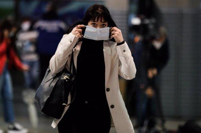 Una pasajera se coloca la mascarilla que previamente le han proporcionado Agentes de la Policía Municipal de Madrid en el intercambiador de la estación Puerta de Atocha, en Madrid (España), a 13 de abril de 2020.