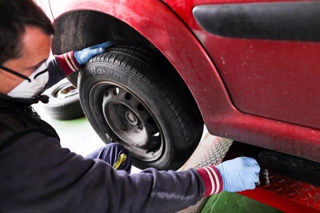 Un trabajador de un taller protegido con una mascarilla arregla la rueda de un coche. El trabajo en los talleres se considera un servicio esencial durante el estado de alarma, pero sólo pueden reparar los vehículos autorizados a circular.