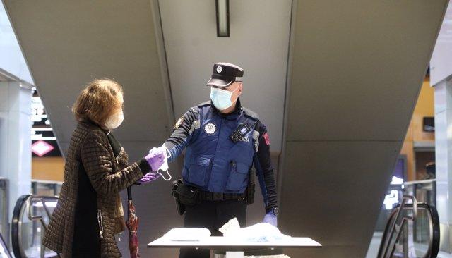 Un agente de la Policía Municipal de Madrid reparte mascarillas a pasajeros en una mesa en el acceso al intercambiador de autobuses de Avenida de América.