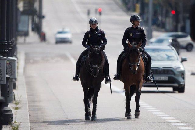Dos agentes de la Policía Nacional vigilan a caballo las calles de la capital durante una Semana Santa atípica en la que prosigue el estado de alarma decretado por el Gobierno para la lucha contra el coronavirus, en Madrid (España) a 8 de abril de 2020