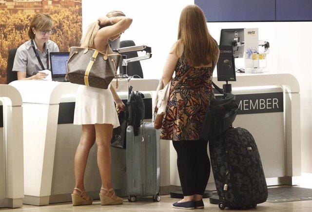 Dos turistas esperan a ser atendidas en el puesto de alquiler de coches