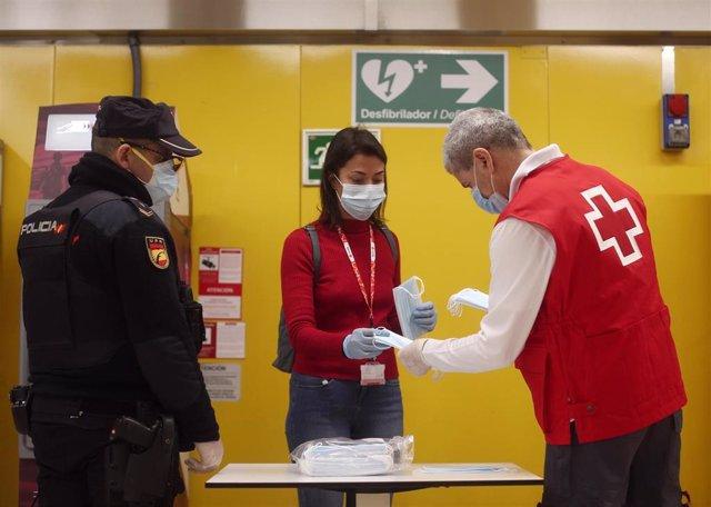Un agente de la Policía Nacional vigila el reparto de mascarillas de un voluntario de la Cruz Roja en el metro de Avenida de América el día en el que se reactiva la actividad laboral no esencial en las empresas cuyos empleados no puedan teletrabajar.
