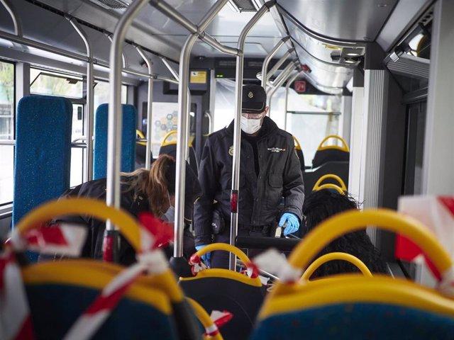 Dos agentes de la Policía Nacional protegidos con mascarillas identifican a viajeros de un autobús urbano en un control en la Avenida del Ejército de Pamplona durante el día en el que se reactiva la actividad laboral no esencial en las empresas cuyos em