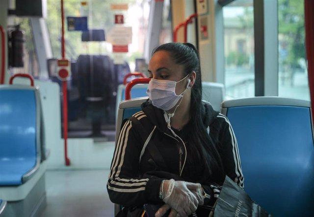 Una mujer con mascarilla en el metro-centro,  el día en el que se reactiva la actividad laboral no esencial en las empresas cuyos empleados no puedan teletrabajar cuando se cumple un mes desde el inicio del estado de alarma decretado a consecuencia del co