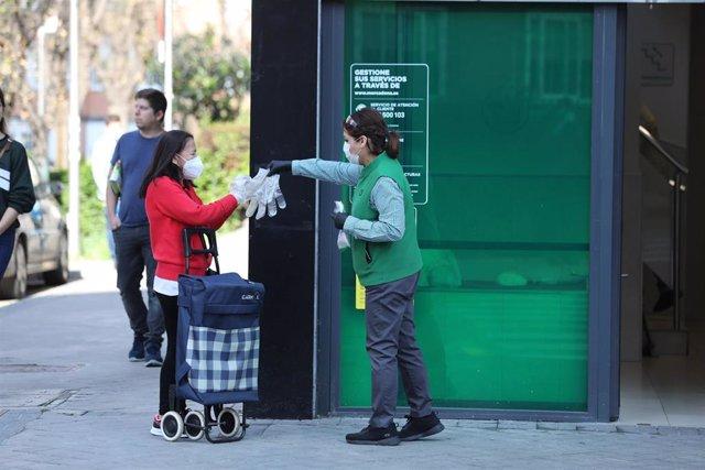 Una trabajadora de un supermercado da guantes a compradores en un supermercado