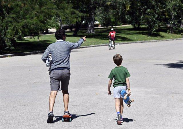 Un padre y un niño con, ambos con patinete, en un parque de Madrid en 2019.