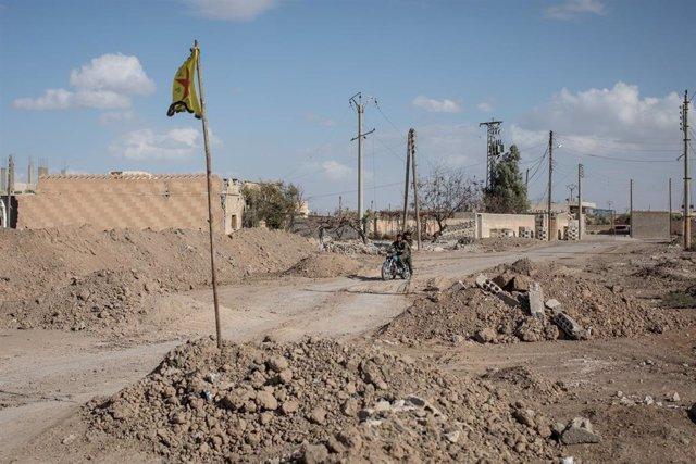 Ruinas en la región de Raqqa y una bandera de las Unidades de Protección Popular kurdo-sirias (YPG)