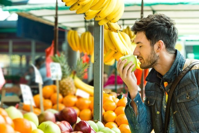 Young man shopping for fruits on the market