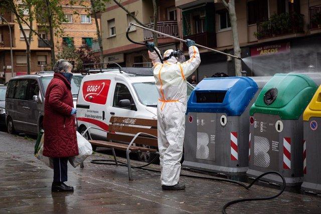 Un trabajador desinfecta y limpia los contenedores de basura de Barcelona durante la tercera semana de confinamiento por la crisis del coronavirus.