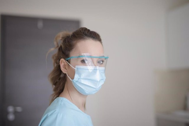 Profesional sanitaria con mascarilla y gafas protectoras.