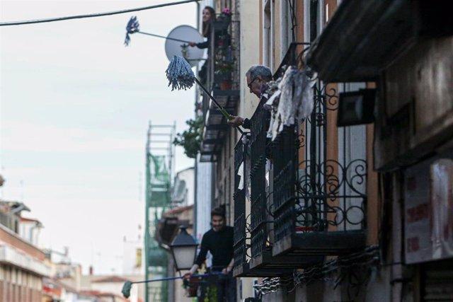 """Vecinos del barrio madrileño de Lavapiés, realizan la 'Fregonada de Lavapiés', un gesto que consiste en agitar fregonas desde sus balcones para """"limpiar el virus"""" cada día después del aplauso habitual a las 20h."""