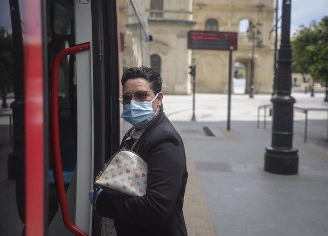 Una mujer con mascarilla entra en el tranvía de Sevilla