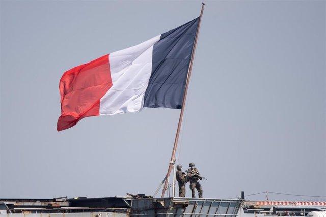 Militares con mascarilla junto a una bandera de Francia