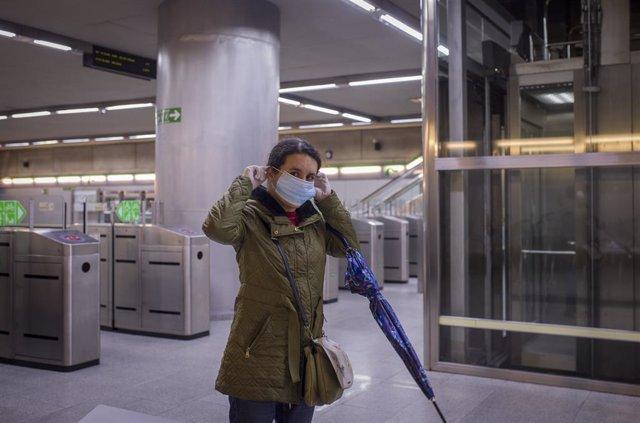 Una dona es posa una màscara al Metro de Sevilla.