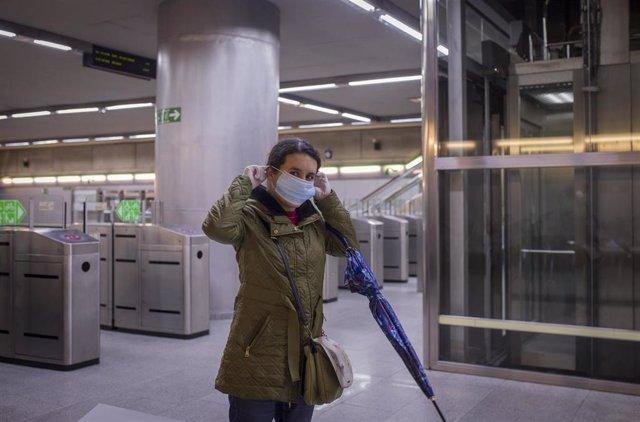 Una mujer se pone una mascarilla tras recibirla de Protección Civil a la entrada del metro de Sevilla.